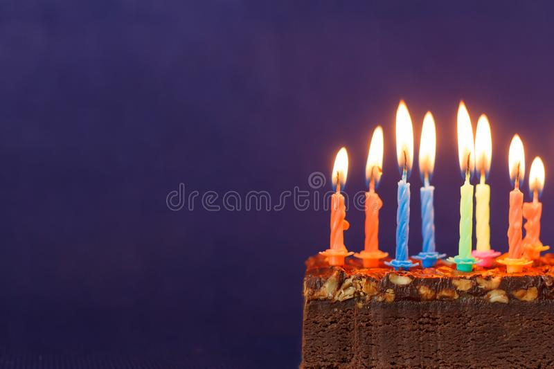 Happy Birthday Brownie Cake with Peanuts, Salted Caramel and Colorful Burning Candles on the Violet Background. Copy Space for. Text lighted unlighted stock photography