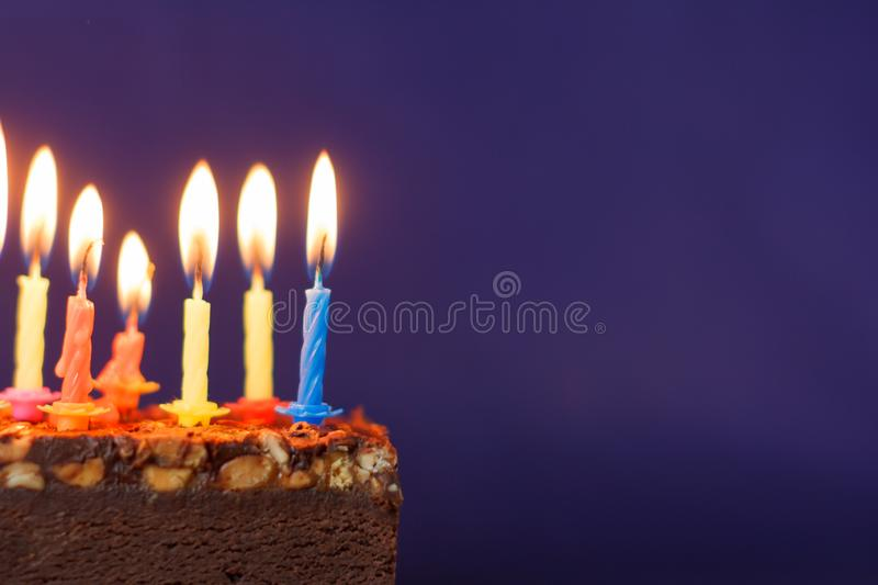 Happy Birthday Brownie Cake with Peanuts, Salted Caramel and Colorful Burning Candles on the Violet Background. Copy Space for stock photo