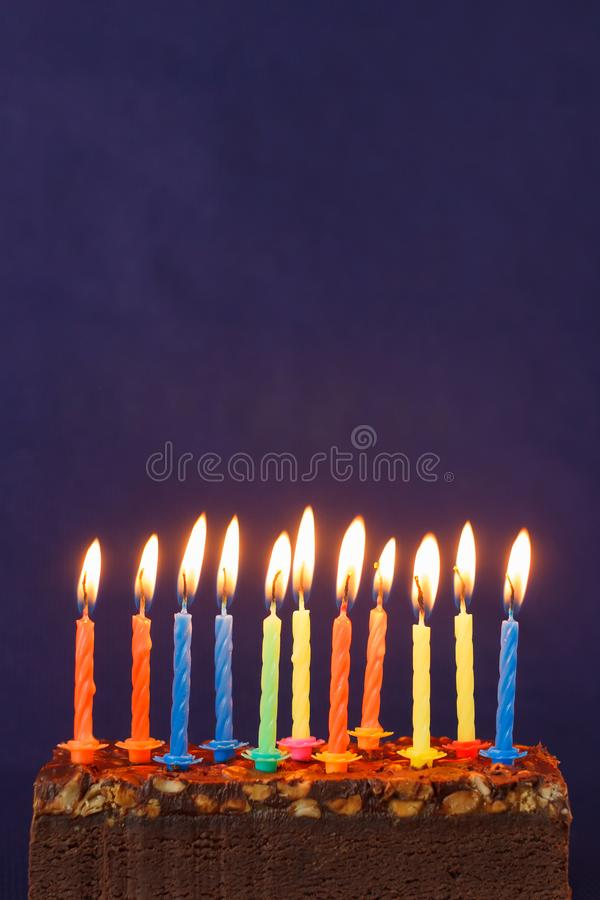 Happy Birthday Brownie Cake with Peanuts, Salted Caramel and Colorful Burning Candles on the Violet Background. Copy Space for. Text lighted unlighted royalty free stock images