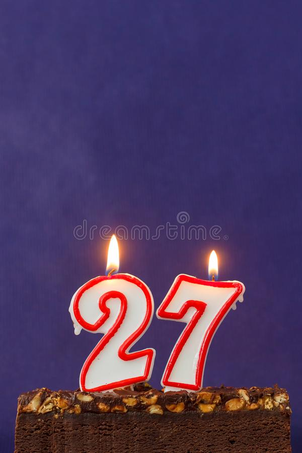 Happy Birthday Brownie Cake with Peanuts, Salted Caramel and Colorful Burning Candles on the Violet Background. Copy Space for. Text. Number 27 lighted royalty free stock photography