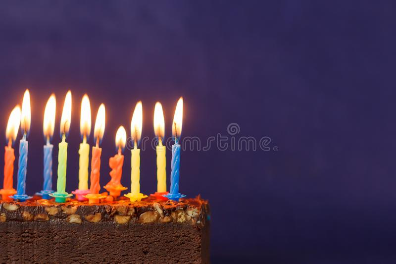 Happy Birthday Brownie Cake with Peanuts, Salted Caramel and Colorful Burning Candles on the Violet Background. Copy Space for stock images