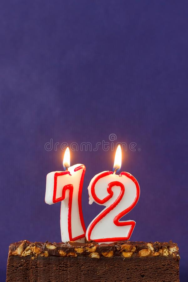 Happy Birthday Brownie Cake with Peanuts, Salted Caramel and Colorful Burning Candles on the Violet Background. Copy Space for royalty free stock image