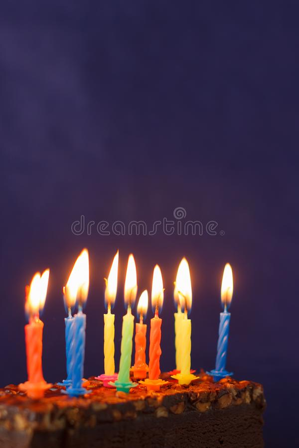 Happy Birthday Brownie Cake with Peanuts, Salted Caramel and Colorful Burning Candles on the Violet Background. Copy Space for royalty free stock photo