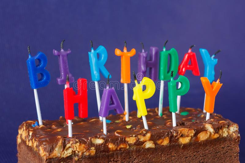 Happy Birthday Brownie Cake with Peanuts, Salted Caramel and Colorful Unlighted Candles on the Violet Background. Copy Space for. Text celebration sweet fire stock photos