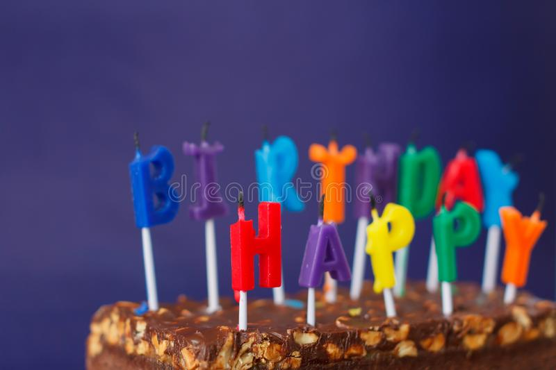 Happy Birthday Brownie Cake with Peanuts, Salted Caramel and Colorful Unlighted Candles on the Violet Background. Copy Space for. Text celebration sweet fire stock photo
