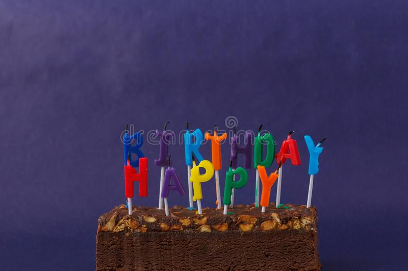 Happy Birthday Brownie Cake with Peanuts, Salted Caramel and Colorful Unlighted Candles on the Violet Background. Copy Space for. Text celebration sweet fire royalty free stock images