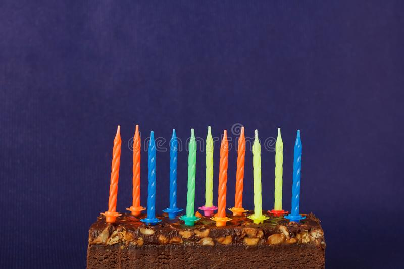 Happy Birthday Brownie Cake with Peanuts, Salted Caramel and Colorful Unlighted Candles on the Violet Background. Copy Space for. Text celebration sweet fire royalty free stock image