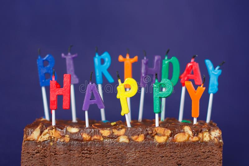 Happy Birthday Brownie Cake with Peanuts, Salted Caramel and Colorful Unlighted Candles on the Violet Background. Copy Space for. Text celebration sweet fire stock photography