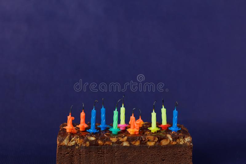 Happy Birthday Brownie Cake with Peanuts, Salted Caramel and Colorful Unlighted Candles on the Violet Background. Copy Space for. Text celebration sweet fire stock images
