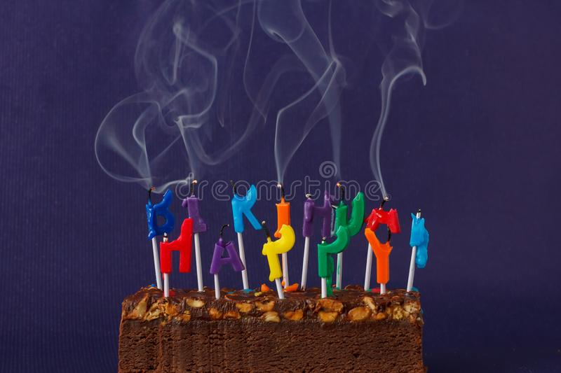Happy Birthday Brownie Cake with Peanuts, Salted Caramel and Colorful Unlighted Smoking Candles on the Violet Background. Copy. Space for Text celebration sweet stock photos