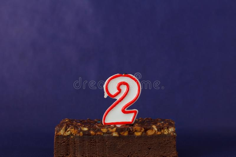 Happy Birthday Brownie Cake with Peanuts, Salted Caramel and Unlighted Candles on the Violet Background. Copy Space for Text. royalty free stock image