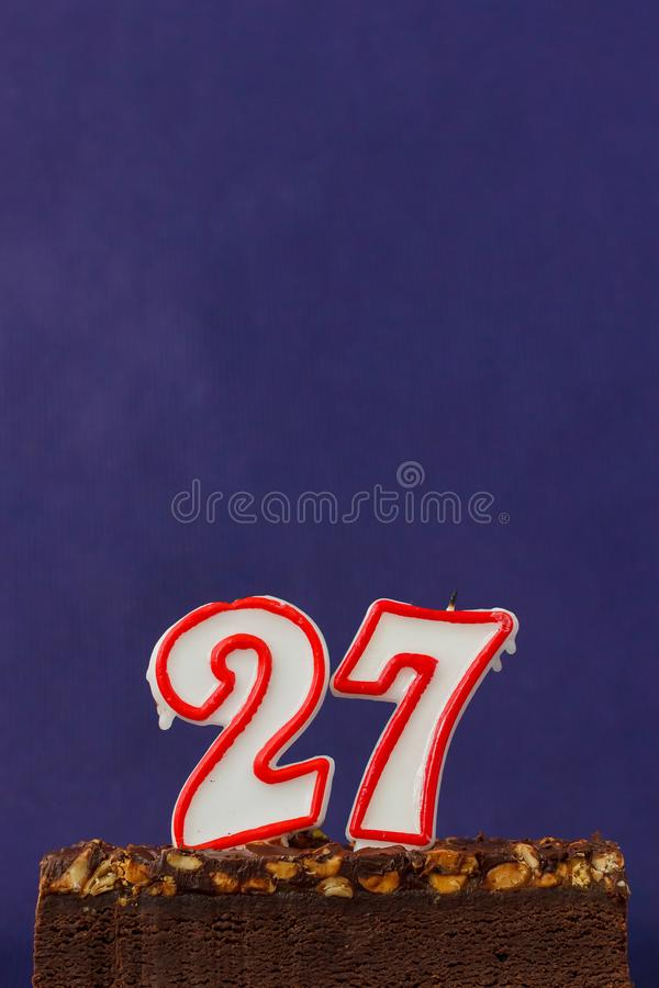Happy Birthday Brownie Cake with Peanuts, Salted Caramel and Unlighted Candles on the Violet Background. Copy Space for Text. Number 27 celebration sweet fire royalty free stock photography