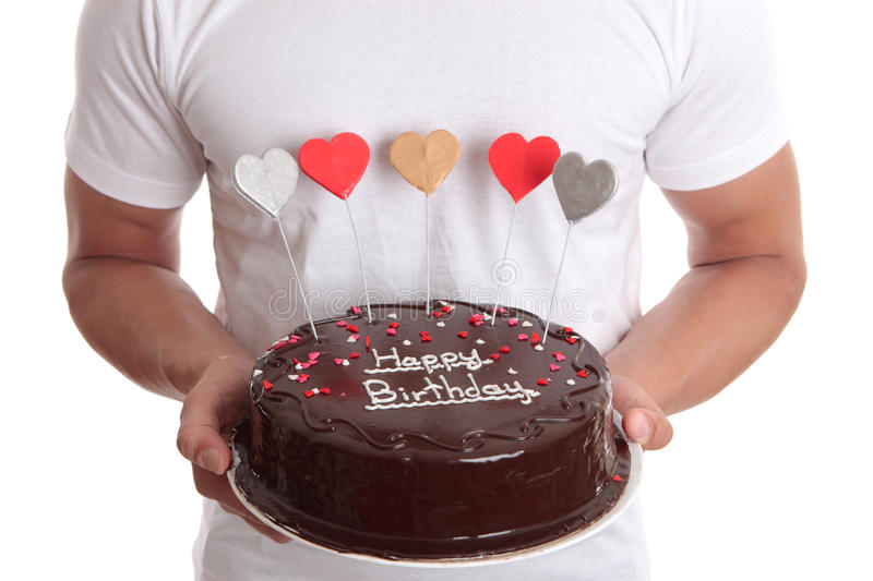 Happy Birthday Cake. Man holding a chocolate birthday cake with lovehearts. Closeup stock image