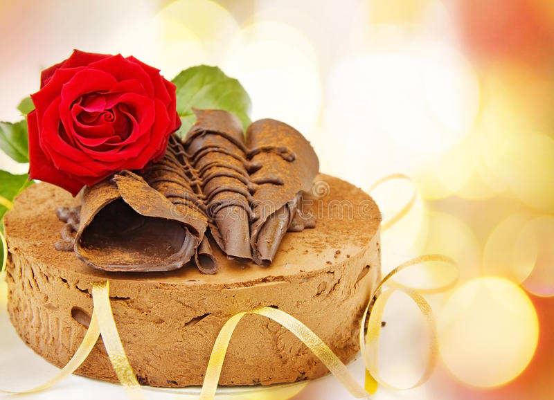 Happy birthday cake. Happy birthday card with toffee cake and red rose over defocused lights royalty free stock images