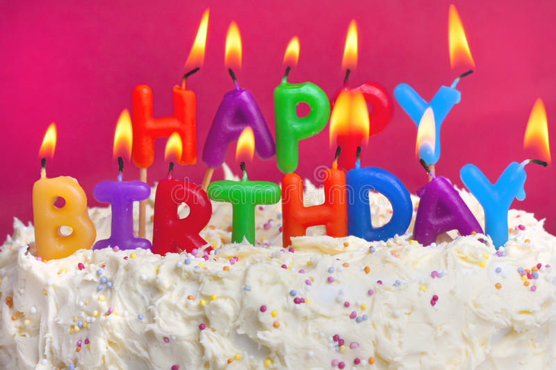Happy birthday cake. Colourful lit candles spellign out happy birthday on a cake royalty free stock image