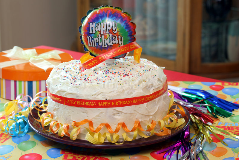 Happy Birthday Cake. Vanilla frosted birthday cake with ribbons all around and a birthday balloon on top stock photo