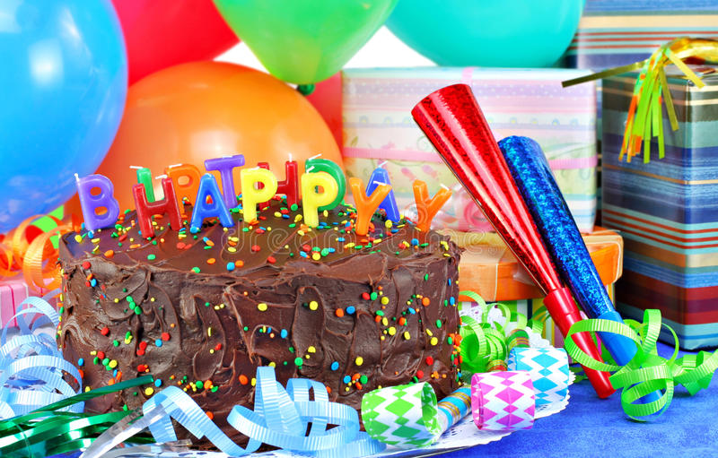 Happy Birthday Cake and balloons. Happy Birthday candles on top of a chocolate birthday cake. Colorful balloons, party horns and gifts surround the pretty cake stock images