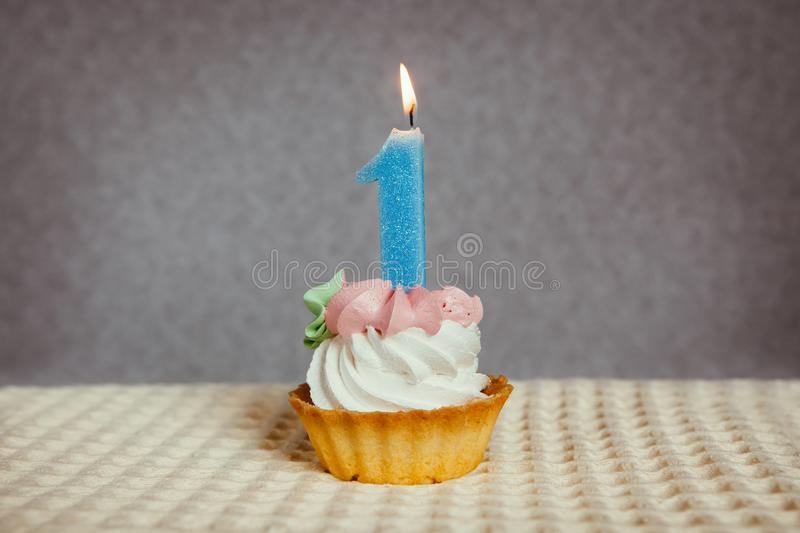 Happy 1 birthday cake and blue number one candle royalty free stock photography