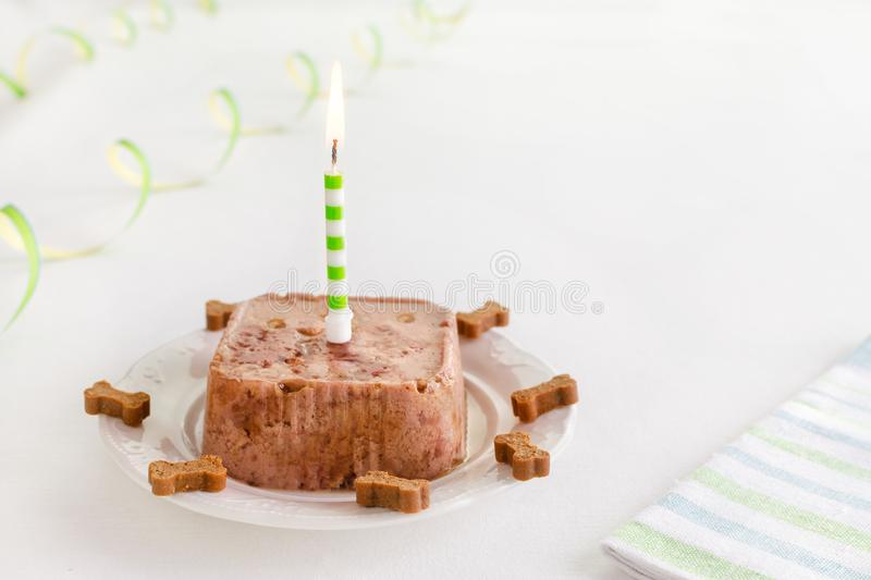Happy birthday cake for dog from wet food and treats with candle and copy space. Happy birthday cake for dog from wet food and treats with candle, copy space stock photos
