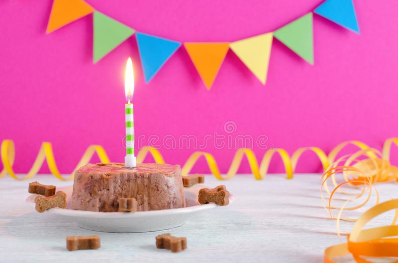 Happy birthday cake for dog from wet food and treats with candle and on pink party background. Selecttive focus royalty free stock photos