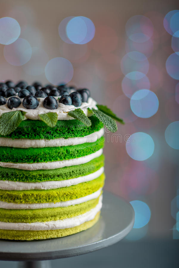 Happy birthday cake. Nice sponge happy birthday cake with mascarpone and grapes on the cake stand on festive light bokeh royalty free stock photos