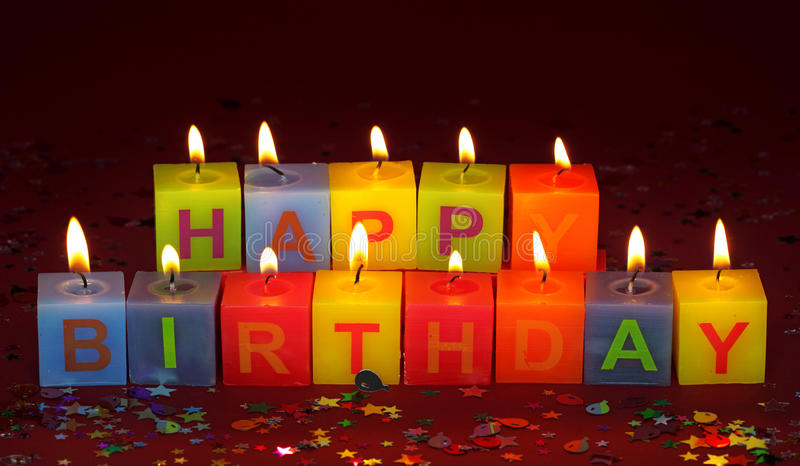Happy birthday candles. Colorful burning happy birthday candles royalty free stock photo