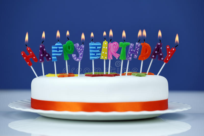 Happy birthday candles on a cake. Happy birthday candles on a white cake over blue background royalty free stock photos