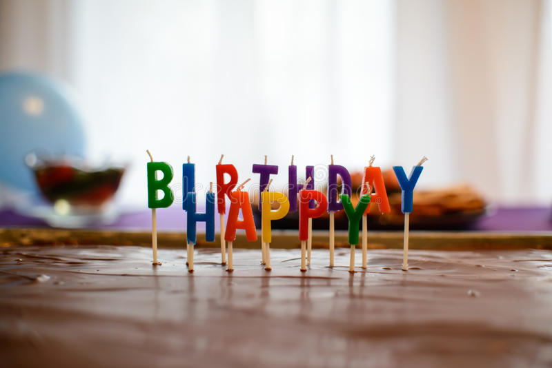 Happy Birthday Candles in chocolate. Lettered happy birthday candles in a chocolate kandy/tandy cake royalty free stock photo