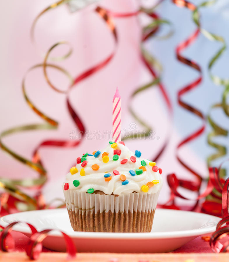 Happy birthday candles cupcake. Serpentine and ball background royalty free stock photos