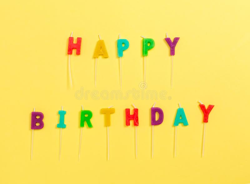 Happy Birthday candles. On a yellow paper background stock image
