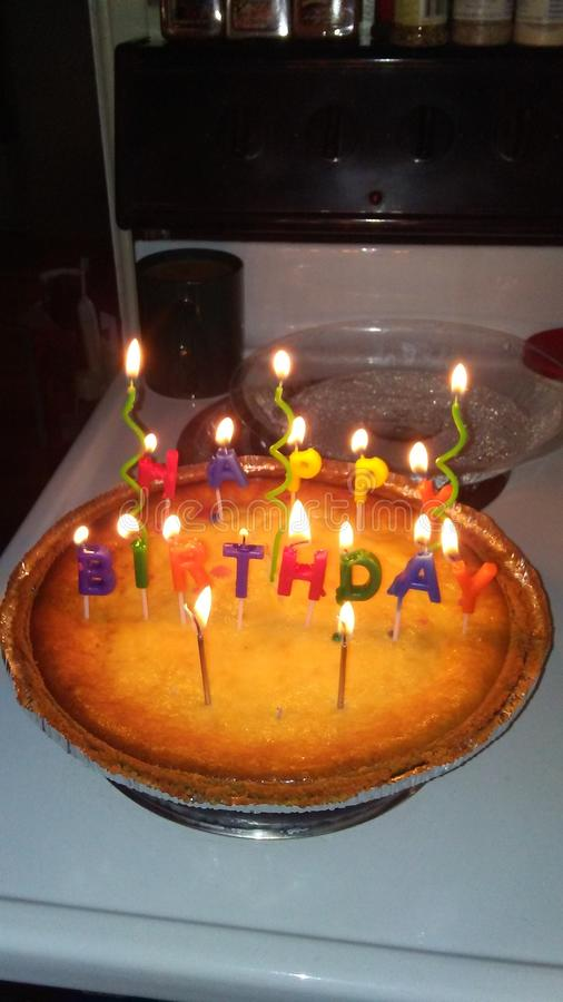 Happy Birthday. Candles lit cheesecake royalty free stock images