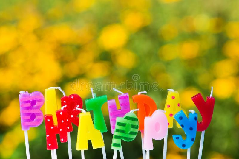 Happy birthday candles on nature background. Colorful happy birthday candles on colorful nature background with flowers stock photo