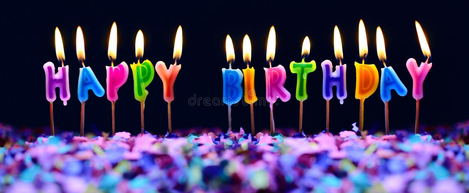 Happy birthday candles and party confetti isolated stock images