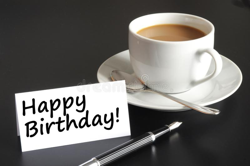 Happy birthday card. Happy birthday greeting card with cup of coffee on black stock image