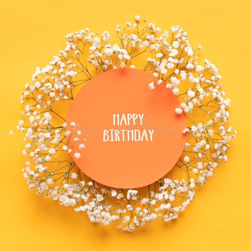 Happy Birthday Card. Flat lay greeting card with beautiful little white flowers on bright yellow paper background. royalty free stock photography