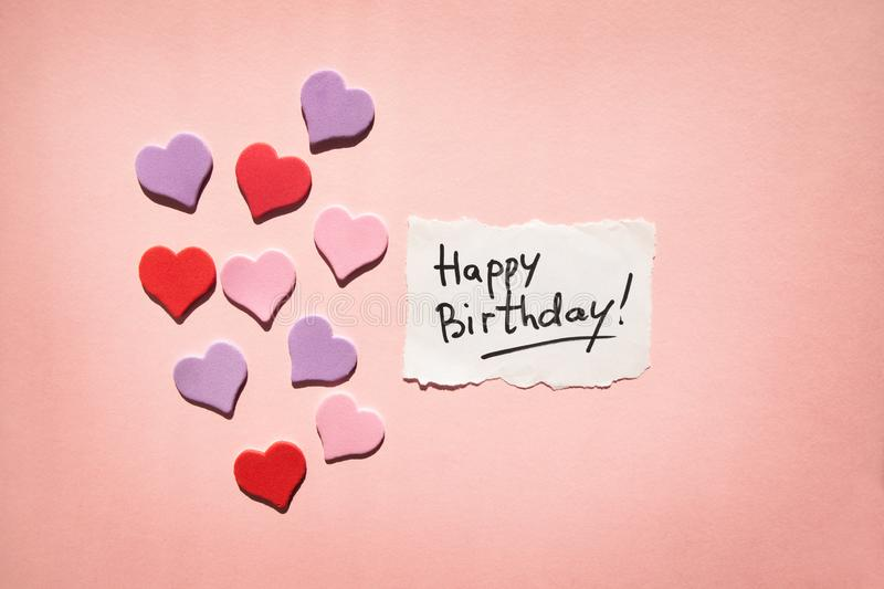 Happy birthday card with text and hearts on beautiful pink background stock photo