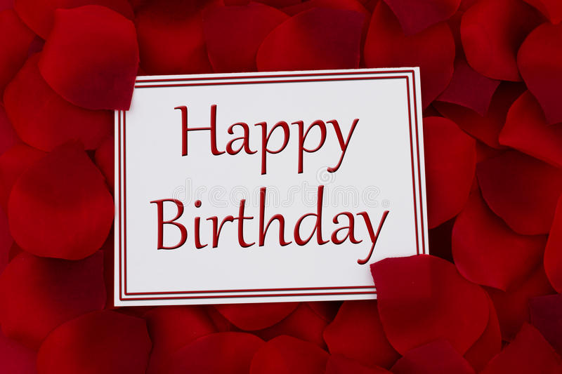 Happy Birthday Card. A white card with text Happy Birthday and a red rose petal backgrounds royalty free stock photography