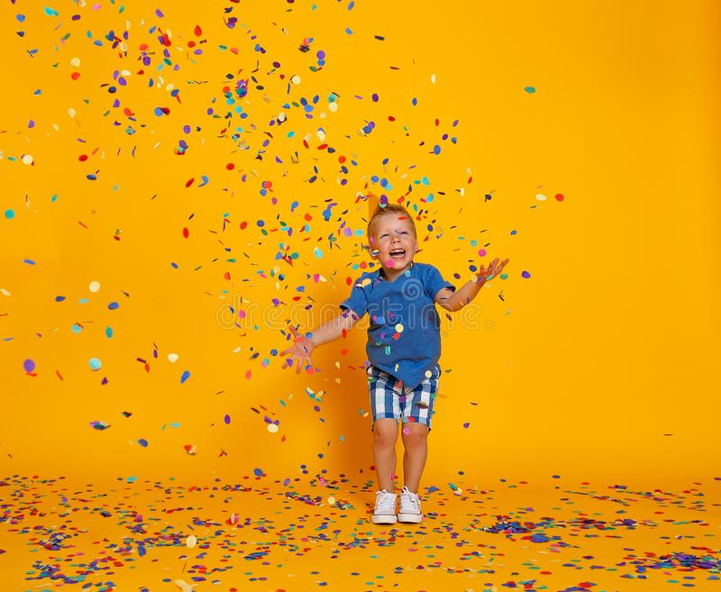Happy birthday child boy with confetti on yellow background. Happy birthday child boy with confetti on  colored yellow background royalty free stock photography