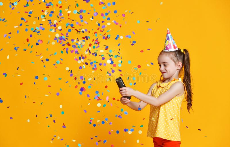 Happy birthday child girl with confetti on yellow background royalty free stock image