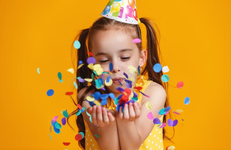 Happy birthday child girl with confetti on yellow background stock photos
