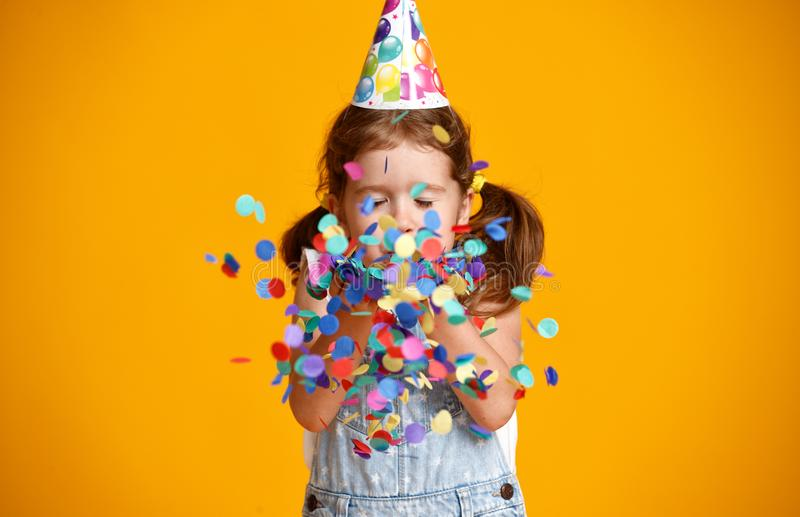 Happy birthday child girl with confetti on yellow background royalty free stock photo