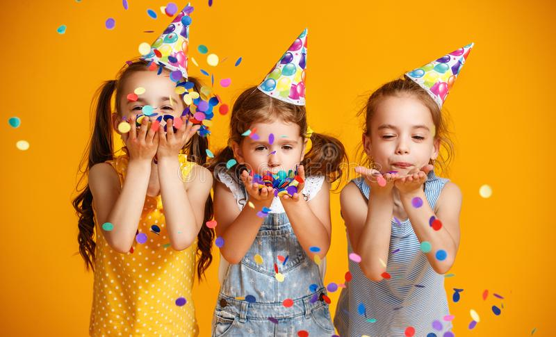 Happy birthday children girls with confetti on yellow background stock photo