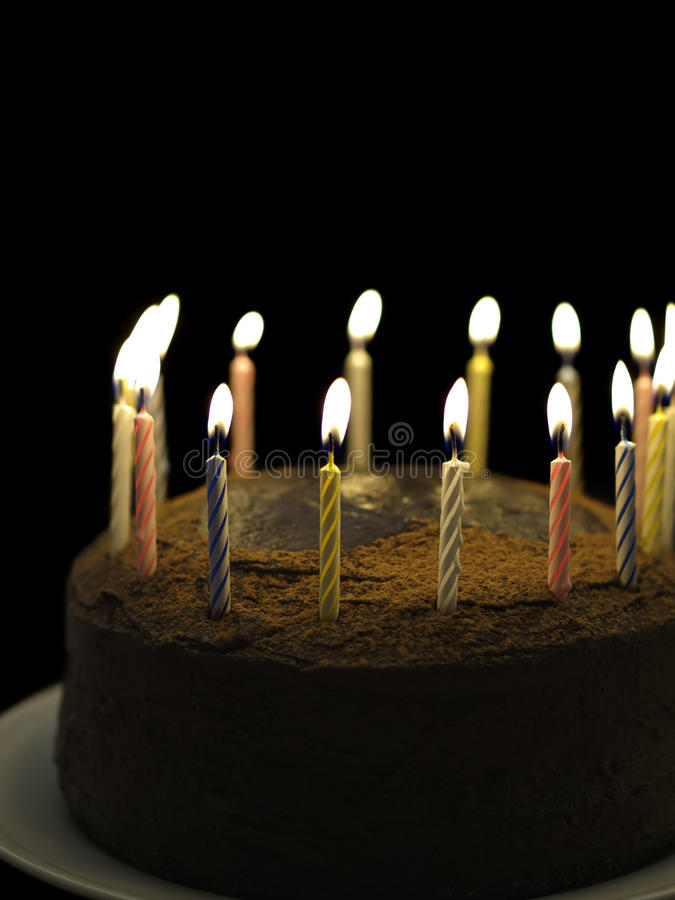 Happy birthday chocolate. Birthday chocolate cake with burning candle on the top. Black background and shallow depth of field royalty free stock image