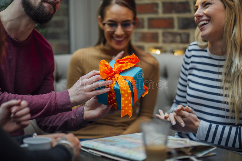 Happy Birthday!. Close up shot of a men passing a birthday present to his friend at her birthday party royalty free stock image