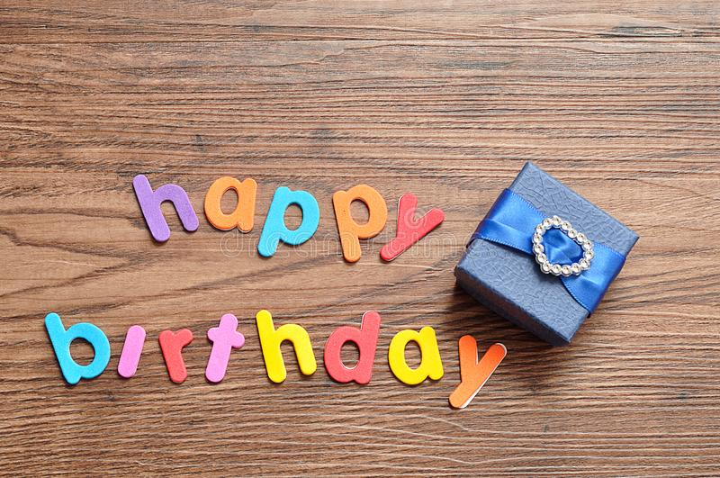 Happy birthday in colorful letters with a blue gift box royalty free stock photos