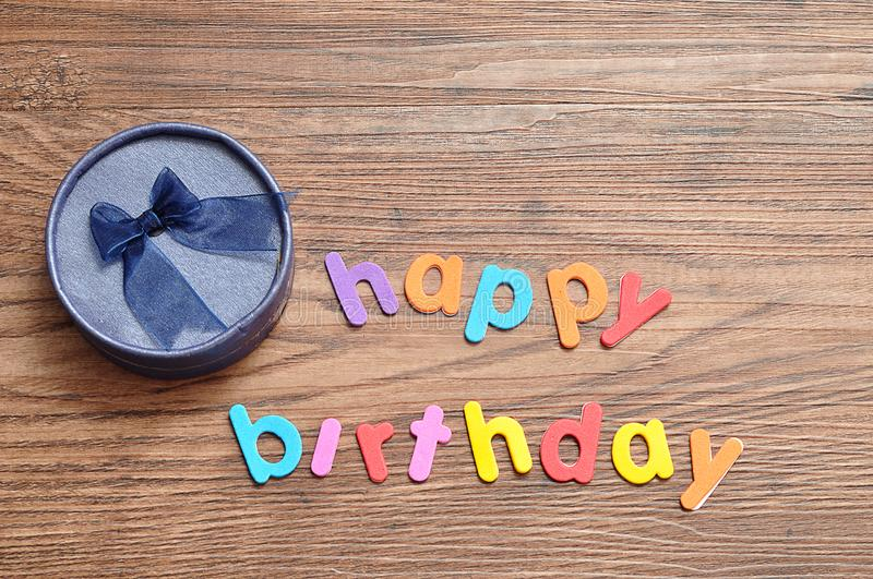 Happy birthday in colorful letters with a blue gift box stock images