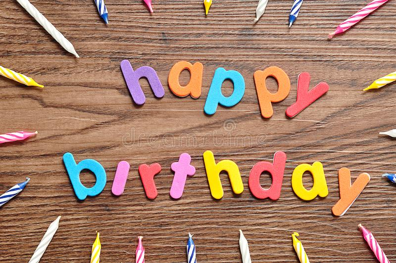 Happy birthday in colorful letters with a collection of birthday candles stock photo
