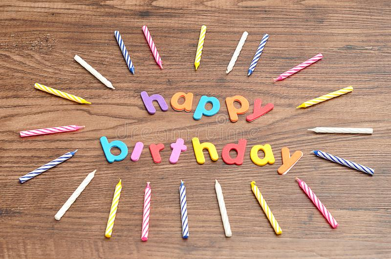 Happy birthday in colorful letters with a collection of birthday candles royalty free stock photo