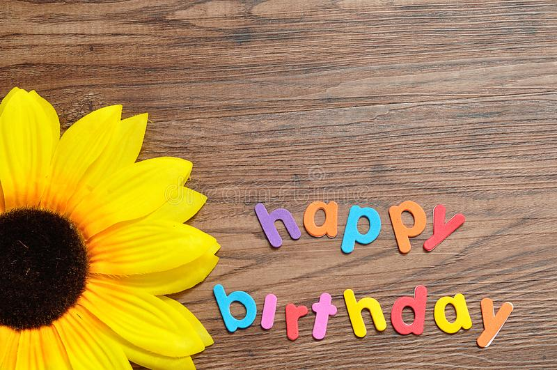Happy birthday in colorful letters displayed with an artificial sunflower royalty free stock photos