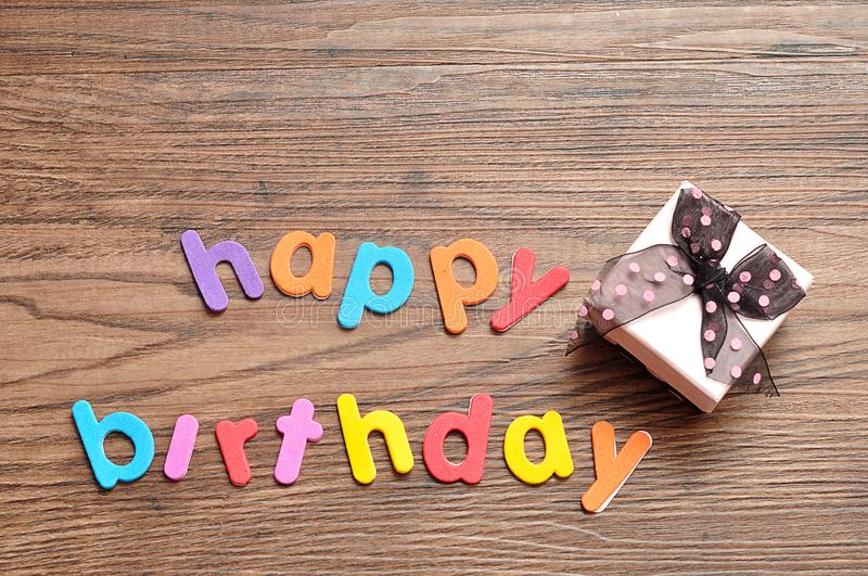 Happy birthday in colorful letters with a pink gift box stock photo